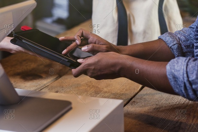 Customer and store owner using a digital tablet for a point of sale transaction