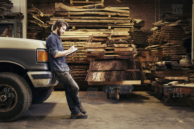 Man leaning against a truck parked inside a carpentry warehouse