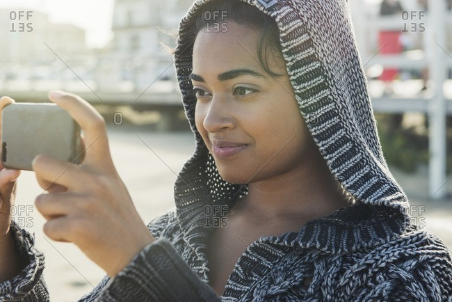 Woman wearing a hooded sweater taking a smartphone photo at the beach