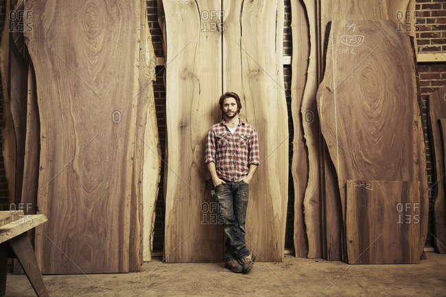 Man leaning against stacks of wood