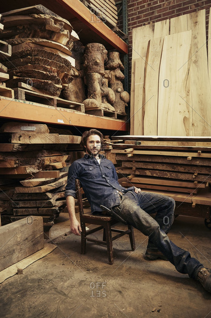 Man sitting in a chair in a warehouse full of stacked wood