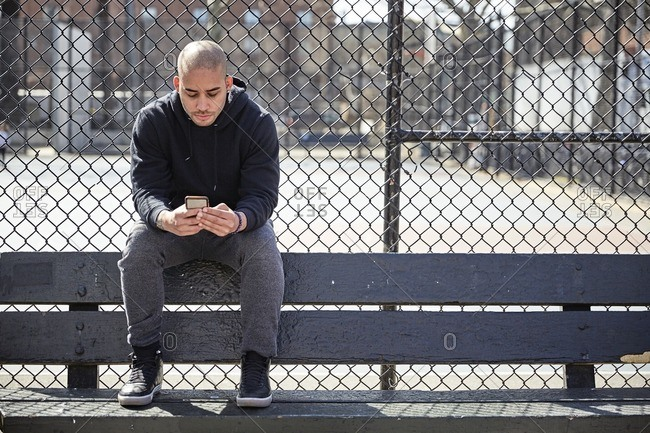 Man wearing a hooded sweatshirt checking his smartphone outside in an urban park