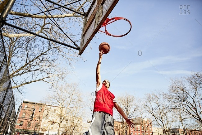 Man doing a layup on a basketball court in an urban park