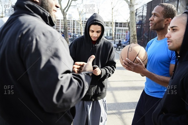Men forming a team for a pick-up basketball game in an urban park