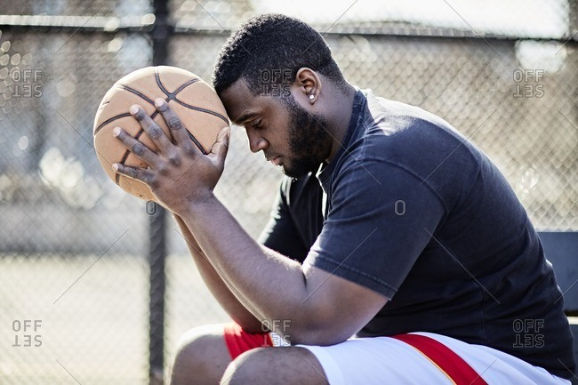 Man sitting on a park bench with a basketball at an urban park
