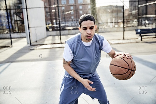 Man dribbling a basketball on a court in an urban park