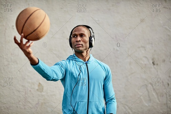 Man wearing headphones and tossing a basketball