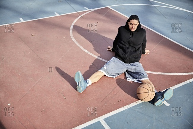 Man sitting with a basketball on a court in an urban park