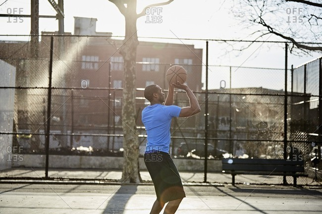Man playing basketball on a court in an urban park
