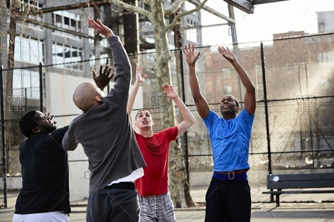 Men playing basketball on a court in an urban park
