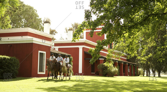 March 18, 2013: Three Argentinian cowboys on horseback in front of red house on ranch