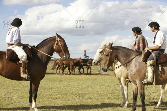 March 18, 2013: Three gauchos on horseback watch man lead horses on ranch