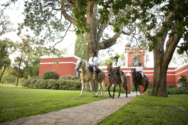 March 18, 2013: Low angle view of three gauchos riding horses near ranch buildings, Argentina
