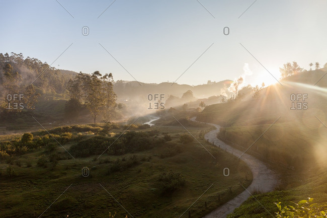 Sun rising over a country road winding through green hills