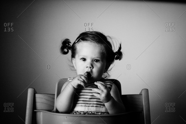 Toddler sitting in a highchair in black and white