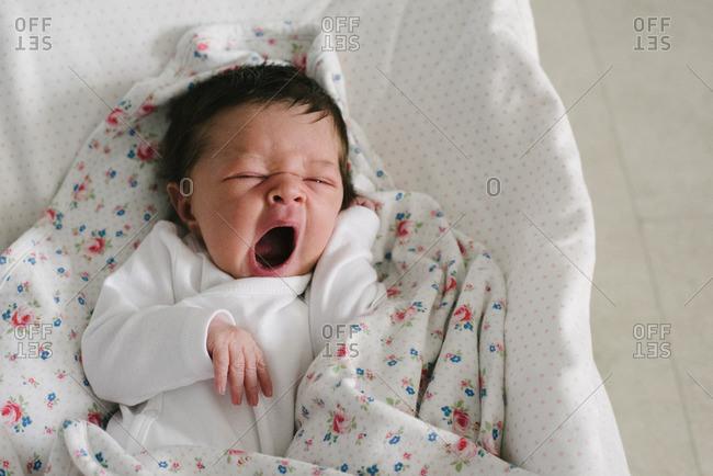Yawning newborn baby lying in bassinet