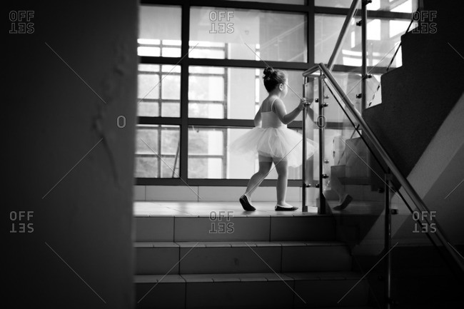 Little girl in a ballerina outfit walking up studio stairs