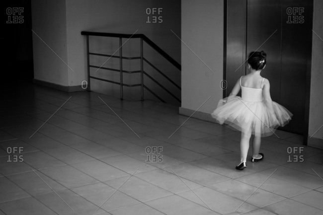 Little girl in a ballerina outfit walking towards an elevator