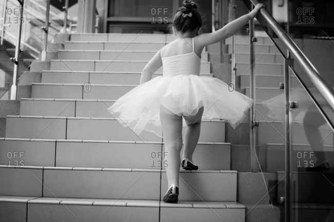 Little girl in a ballerina outfit walking up stairs