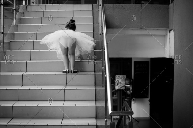 Little girl in a ballerina outfit standing on stairs