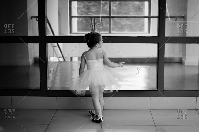 Little girl in a ballerina outfit looking out studio window