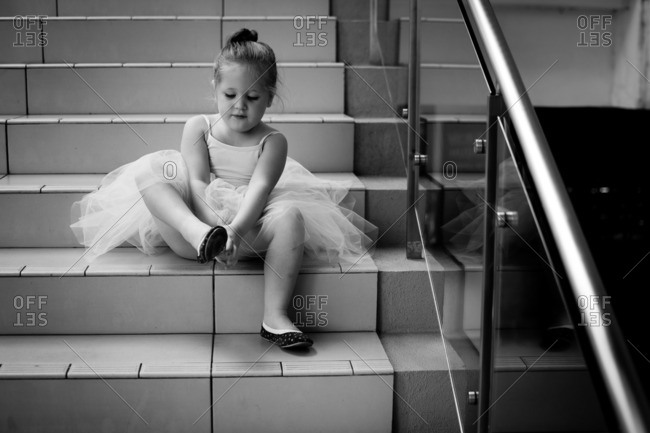 Little girl in a ballerina outfit sitting on stairs