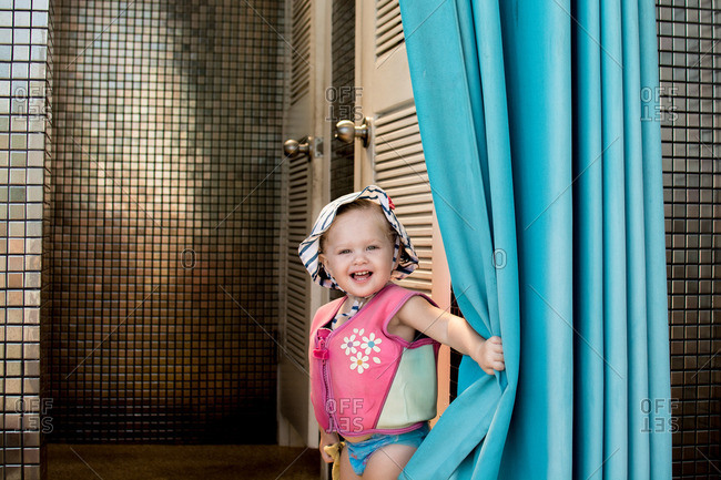 Toddler girl getting into outdoor shower