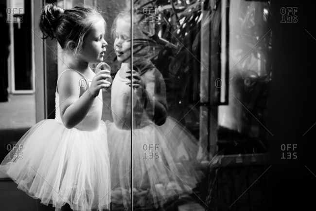 Girl in ballerina outfit looking at her reflection in the studio window