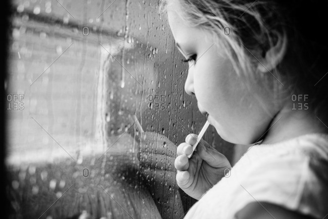 Young girl eating a lollipop and looking out a rain-streaked window