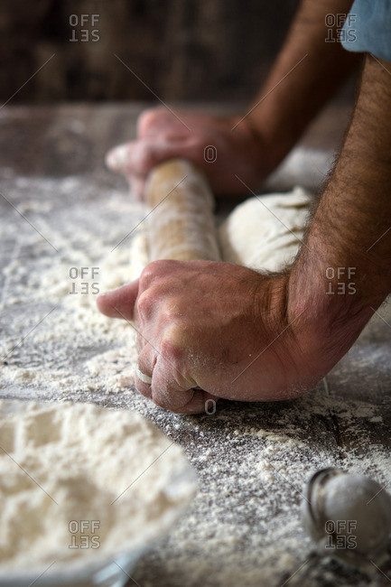 Man rolling out dough with rolling pin
