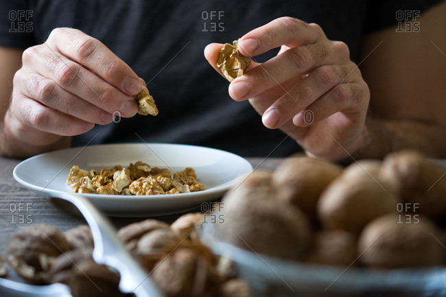 Hands cracking walnuts and separating it from the shell