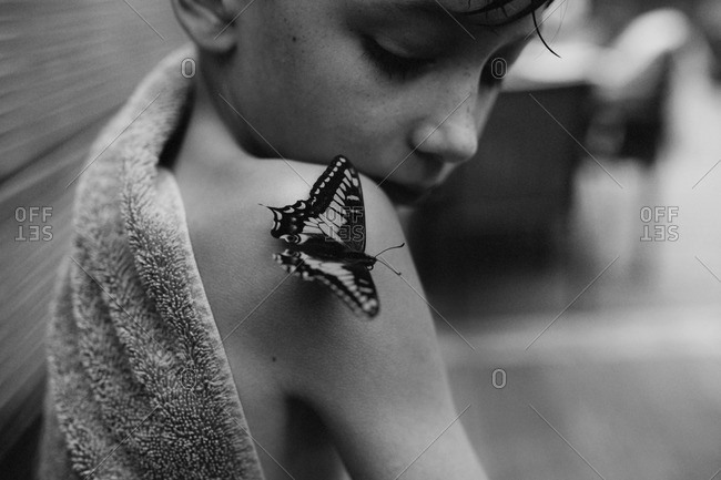 An anise swallowtail on a boy's shoulder