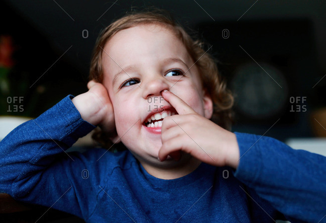 Toddler picking his nose with other hand on head