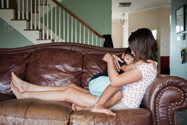 Mother holding her son while on the couch