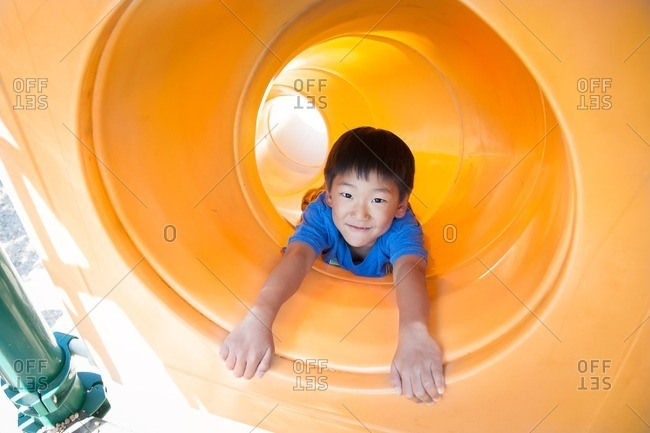 Boy at the bottom of a tube slide on a playground