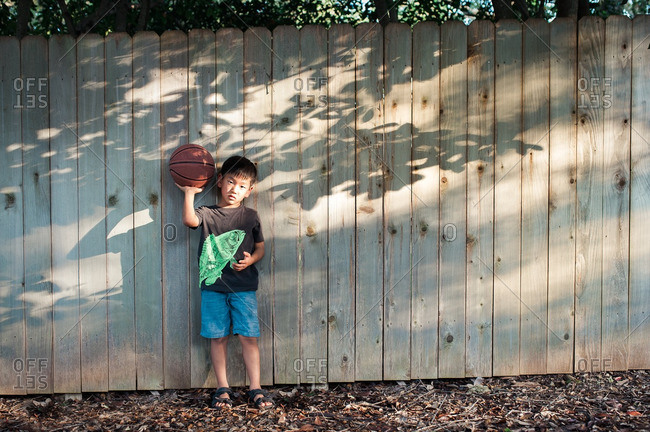 Boy holding a basketball while standing against a fence