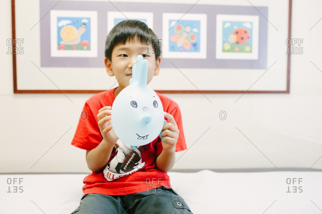 Boy holding an inflated surgical glove with a face drawn on it while at the doctor's office