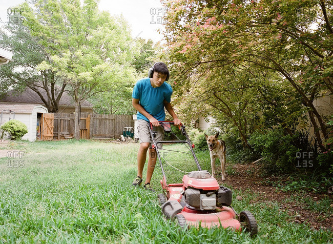 Teen boy mowing the lawn while wearing headphones as the dog stands nearby