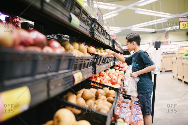 Boy picking out fresh produce at the supermarket