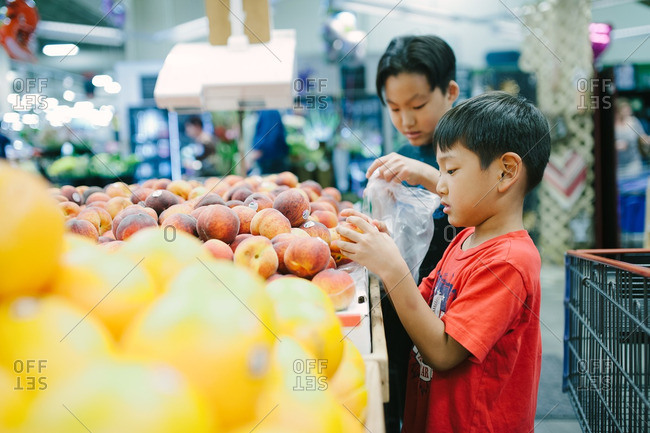Two boys picking out fresh produce at the market