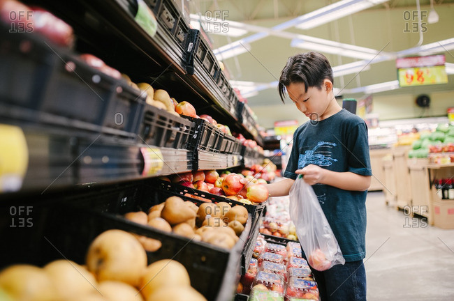 Boy selecting apples at the supermarket