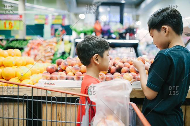 Two boys selecting fresh fruit at the supermarket