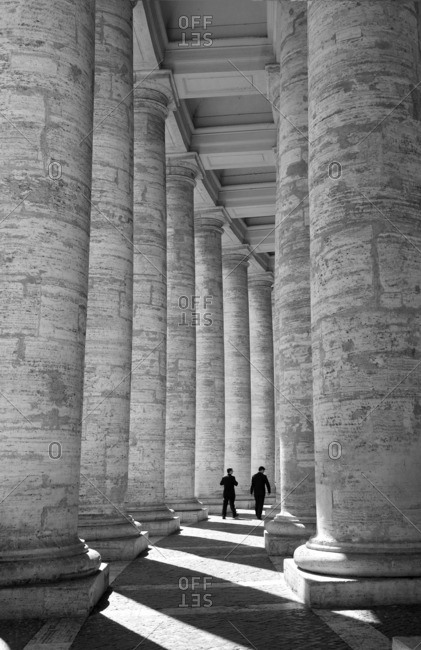 Two priests walking between colonnades in Vatican City, Rome, Italy