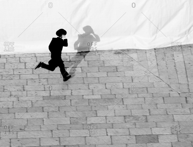 Young Orthodox Jewish man running to catch the bus in Jerusalem, Israel