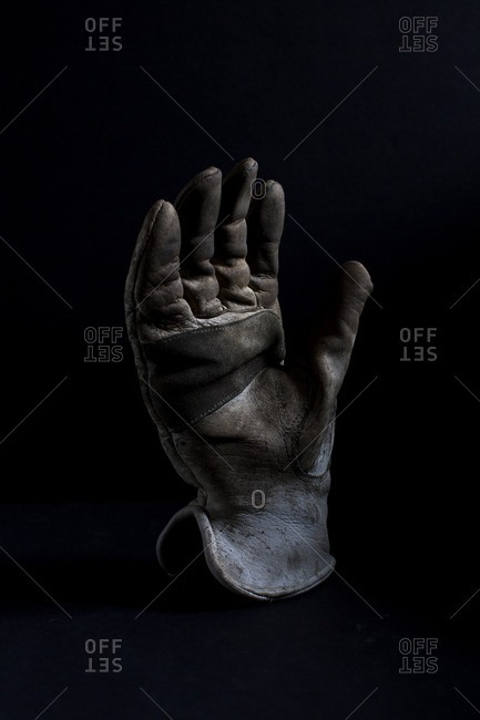 A used welder's glove on a black seamless background