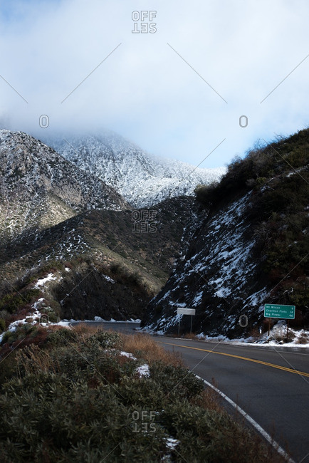 Road running through snowy mountains in California