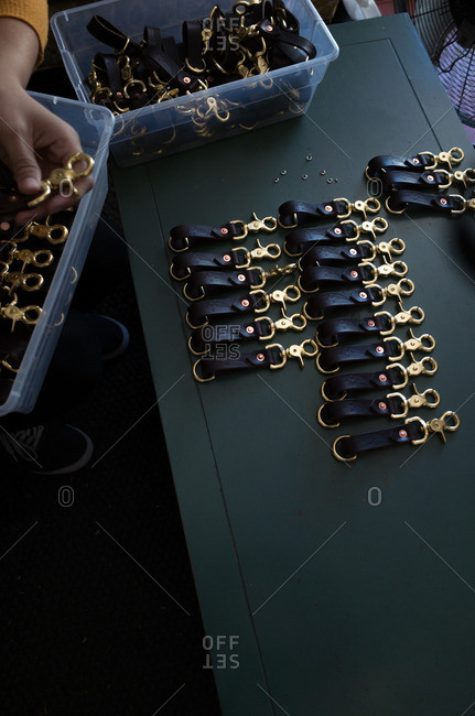 Person sorting through leather key chains