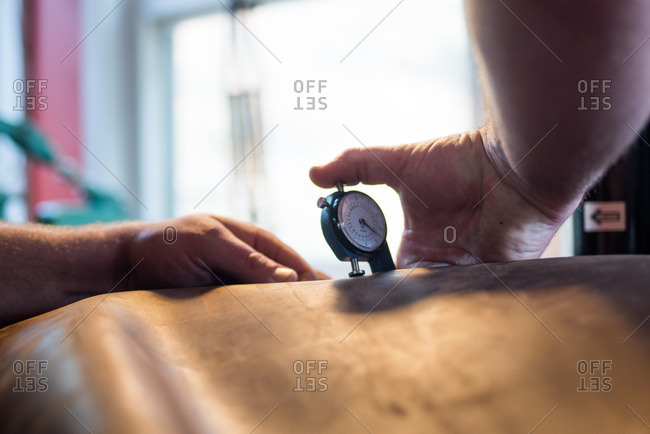 Person using leather gauge