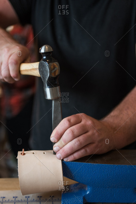 Person working with leather, hammer and chisel