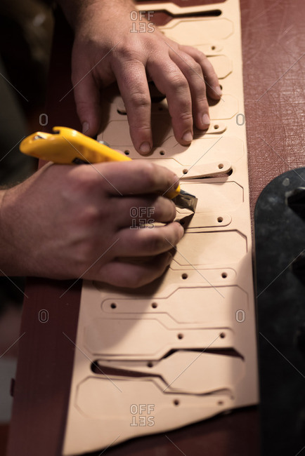 Person cutting leather with a utility knife